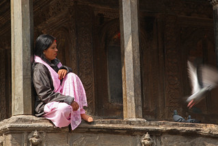 Woman sits on a ledge at a temple in Kathmandu | by World Bank Photo Collection