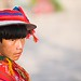 Young Quechua boy in traditional clothing and hat, with red woven cloth, side view, Peru, Ollantaytambo