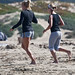 Two females, possible a mother daughter team, jog barefoot on the Morro Strand Beach