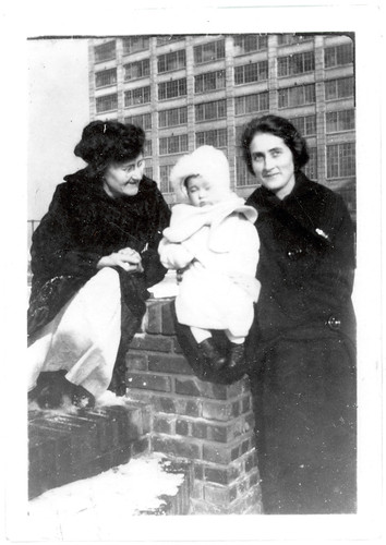Two women on a rooftop with a baby