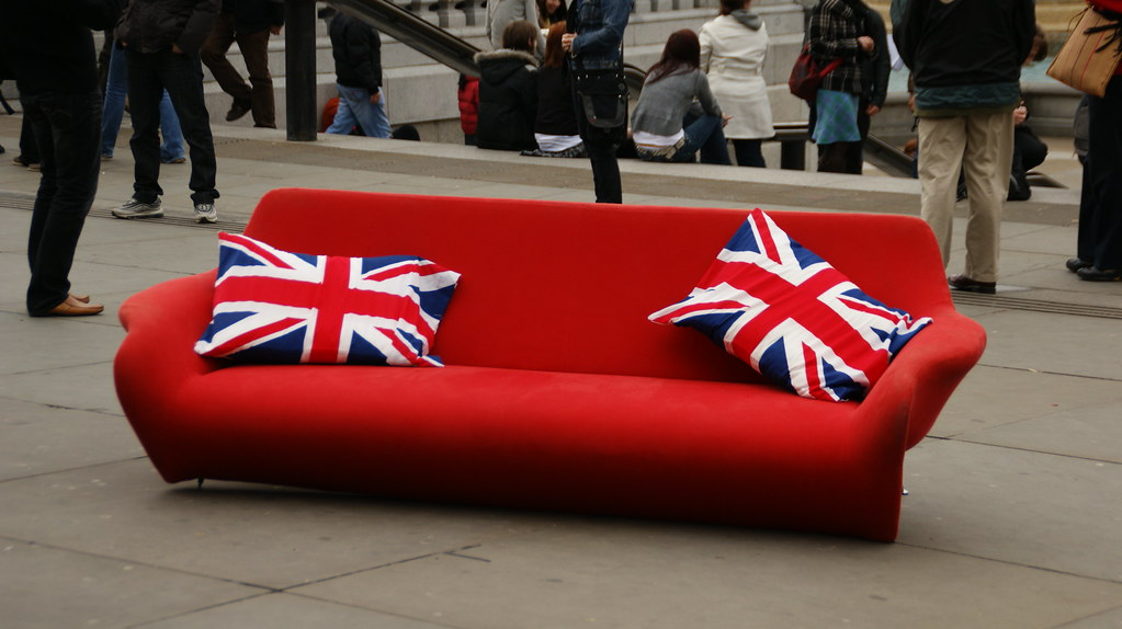 Red Couch On Display With British Flag Cushions On Trafalg