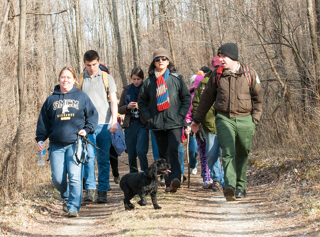 Hikers enjoying a First Day Hike, led by a ranger and accompanied by a dog