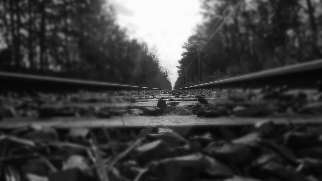Railroad Tracks Backlit With A Nice Sky Black And White