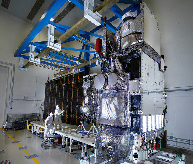 Integrated GOES-S satellite in a clean room, with solar array deployed.