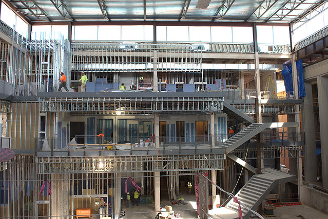 A photo showing all the floors of the Mell Classroom Building as they are under construction, with the grand staircase to the right in the photo.