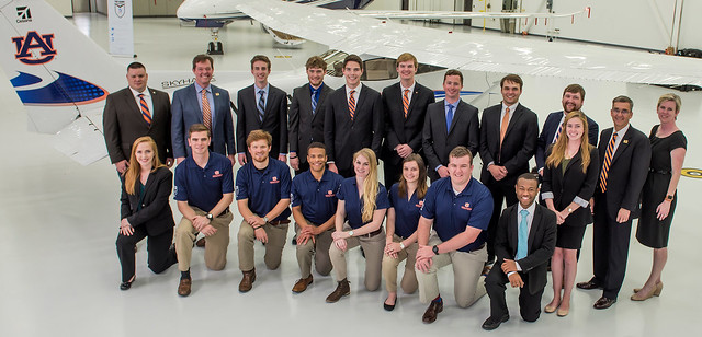 A group of Auburn students and officials stand and kneel in front of a new Cessna Skyhawk 172 aircraft.