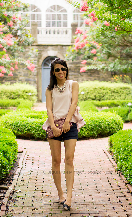 pearl and mixed metal necklace, pink peplum top, navy shorts, rose pink clutch, bow ballerina flats