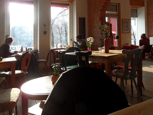 Ziemlich leeres CaféinKreuzberg, durch dessen Fenster die winterliche Vormittagssonne fällt
