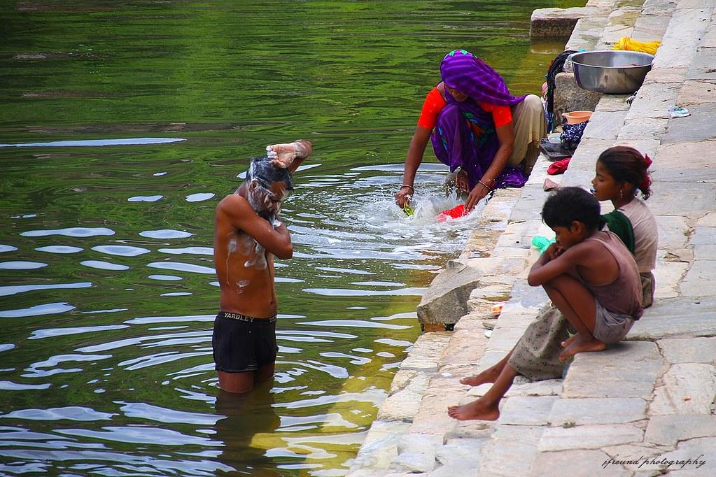 village women bathing and washing clothes udaipurindia
