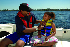 Father securing child's life jacket.