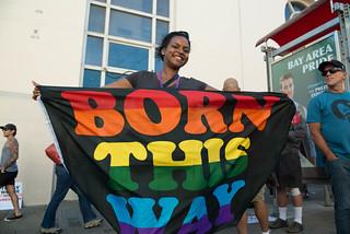 Mujer sosteniendo bandera que dice: 'Born This Way', nací de esta manera.
