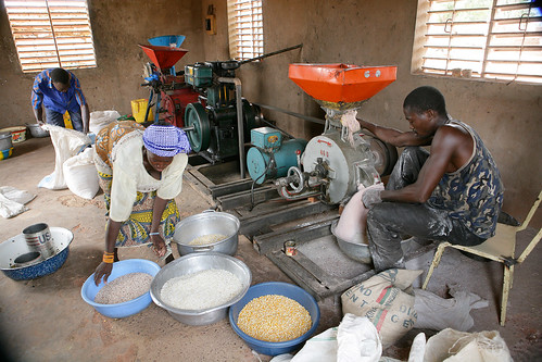 A woman and man process corn using the Multifunctional Platform Engine in Burkina Faso | by United Nations Development Programme