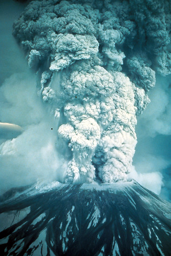Image shows the shorn-off summit of Mount St. Helens with a huge column of ash boiling up into the sky. It looks like a monochrome image because the ash has shut out the sun and turned everything various shades of gray.