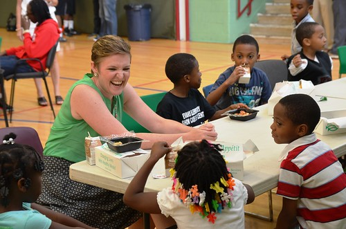 USDA Center for Faith-Based and Neighborhood Partnerships Director Norah Deluhery eating lunch with kids at a Philadelphia Archdiocese's Nutritional Development Services (NDS) summer food service site.