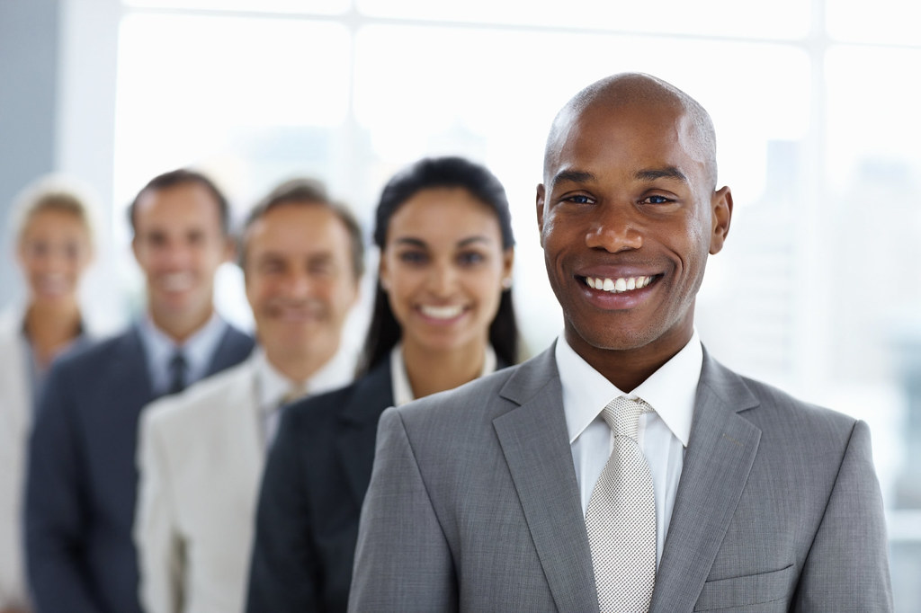 Happy African American business man with colleagues in a l ...