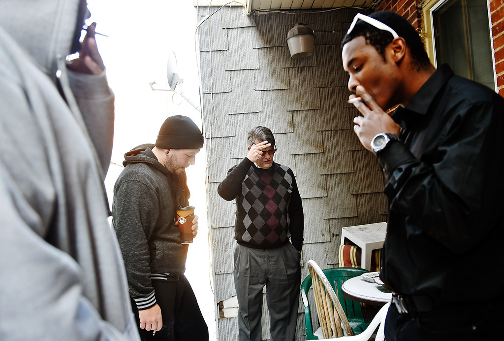 © 2016 by The York Daily Record/Sunday News. Dave Dunkel, owner of Sees-the-Day, center, shares a cigarette break with, from left, Zachary Moser, 21, of Montgomery County, Pa.; Nathan Embry, 27, of Lancaster; and Roman Fissel, 22, of Manchester Township, all of whom live in a Sees-the-Day recovery house on Linden Avenue, on Wednesday, Feb. 10, 2016. Many recovering addicts are smokers, as cigarettes and nicotine replace the addictions from which they are recovering. York is home to a figuratively underground community of about 80 recovery homes that house drug and alcohol addicts. Many recovering addicts are sent to the houses by York County's probation department as an alternative to jail or homelessness, while other addicts come to York on referral from other treatment facilities or of their own volition. The houses, which are not designed as treatment programs and which can each house 5-12 recovering addicts, are not subject to state or county regulations . While owners of many recovery houses in York refused comment, other owners said their homes are structured to provide a system of support and accountability by requiring residents to attend 12-step meetings and gain employment, with the ultimate goal of graduating sober after a residency of about six months.