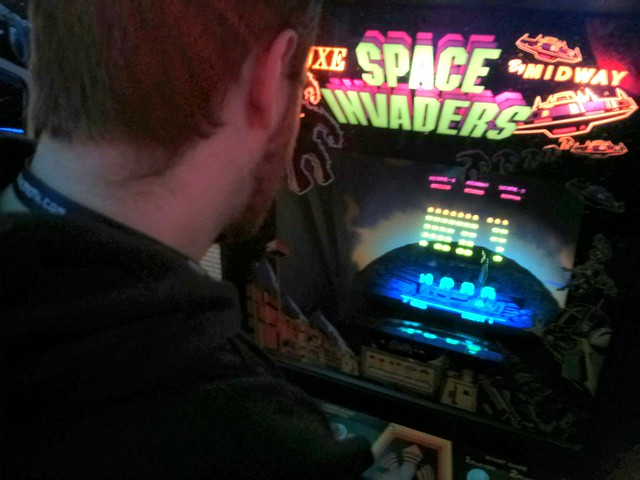 picture shows a male using a space invaders machine