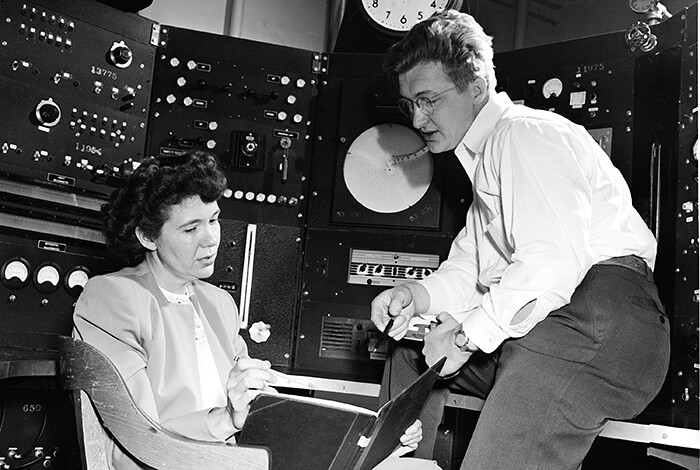 A man and a woman sit in a control room; the woman looks at a book.
