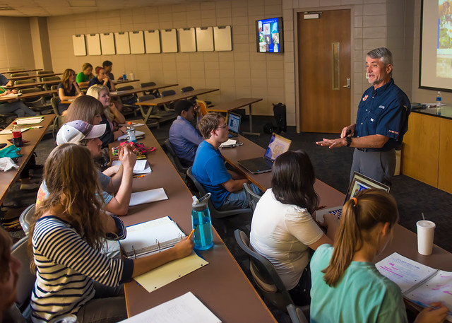 Biology Professor Robert Boyd stands at the front of a lecture-style classroom and teaches to rows of students.