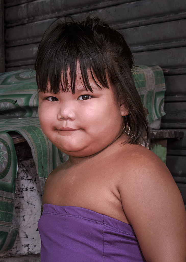 Button Nose Grin A Young Filipina Child Sports A Shy