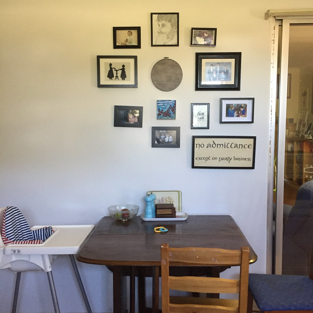 table with a couple of chairs and a high chair, with a wall of black framed pictures and artworks