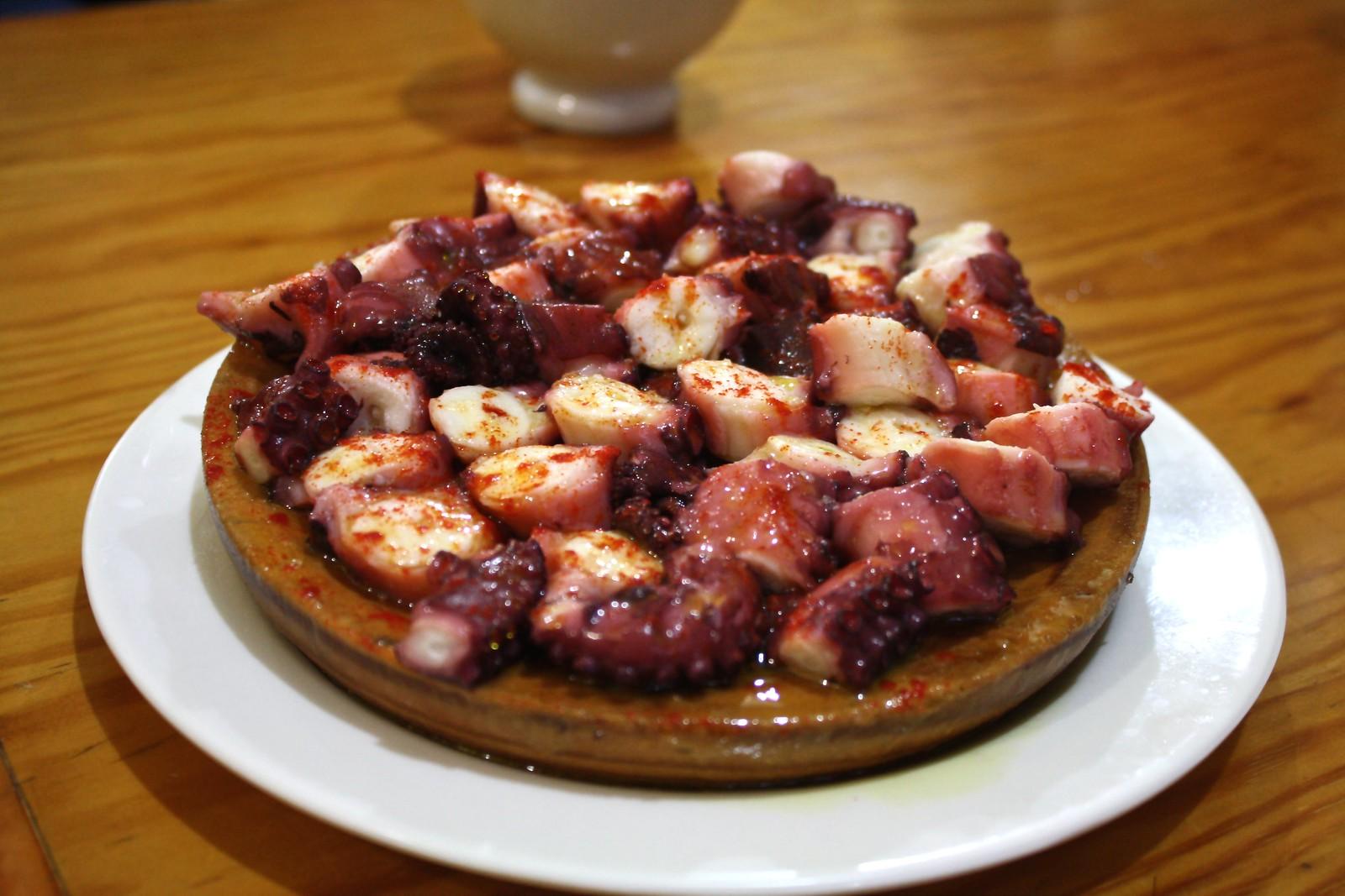 A wooden plate of boiled octopus at Bodegón Os Concheiros, Santiago de Compostela, Spain