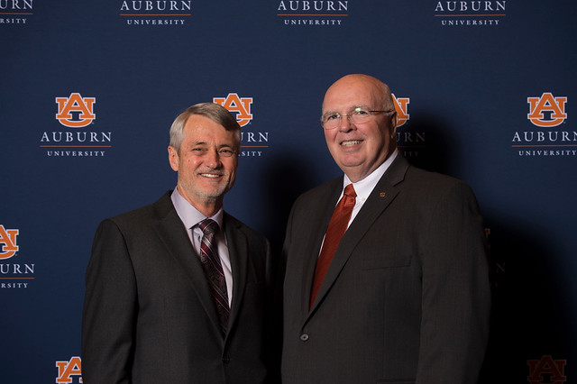 Biology Professor Robert Boyd and Provost Timothy Boosinger pose for a photo in front of a navy Auburn University backdrop.