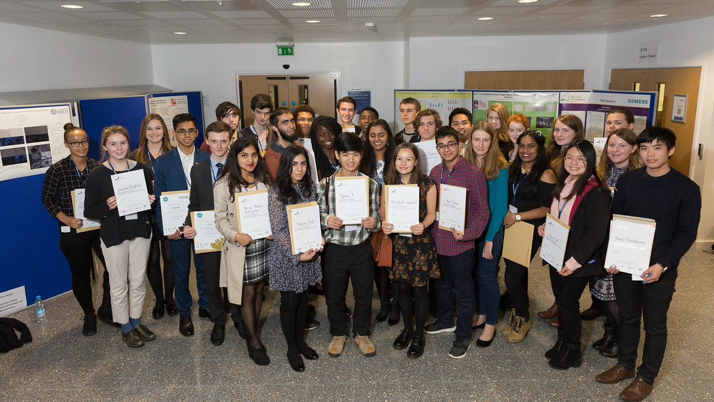 Nuffield Research Placement students in a group shot holding their certificates up in front of them.