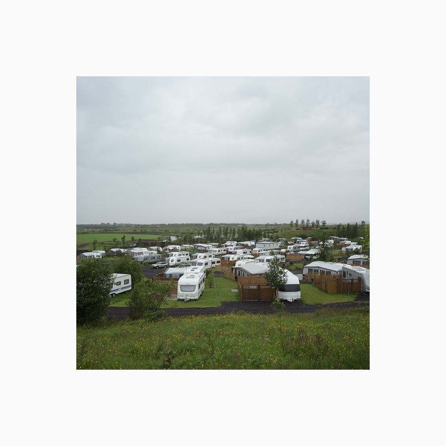Mobile homes, caravans, all white at a campsite.
