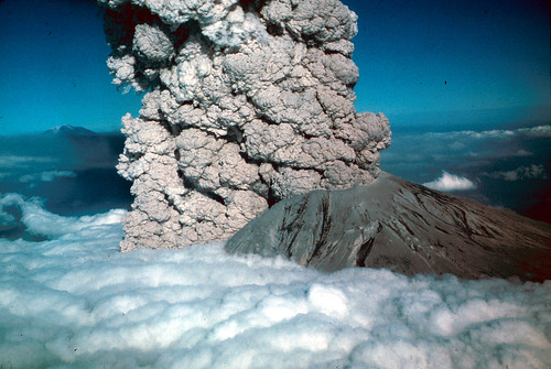 Image is a vivid color photo of Mount St. Helens from the air. The new, truncated summit of the volcano pokes above a fluffy white sea of clouds. A huge, roaring wall of dark gray ash is pouring from the crater and the gap in the crater wall.