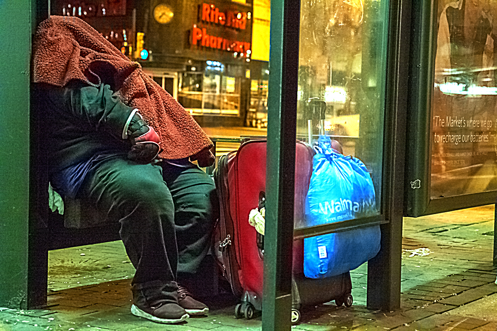 Man-sleeping-at-bus-stop-shelter-on-9-14-14--Center-City