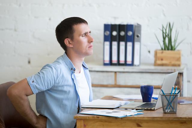 Mann mit Rückenschmerzen im Büro