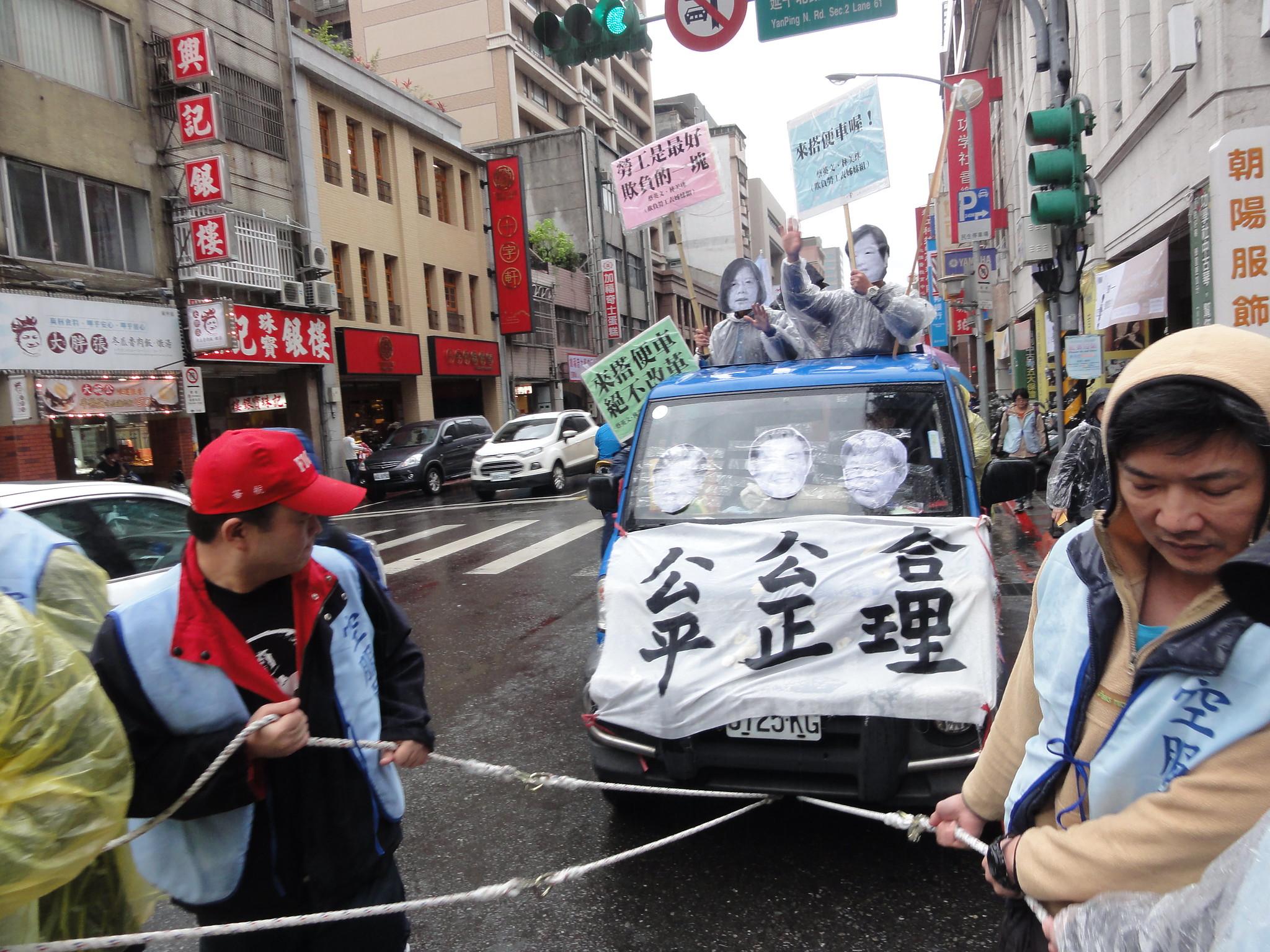 勞工拉著「蔡英文」和「林美珠」前進,車上的兩人在宣揚「搭便車」。(攝影:張智琦)