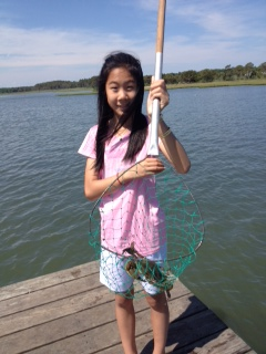 Girl with netted blue crab