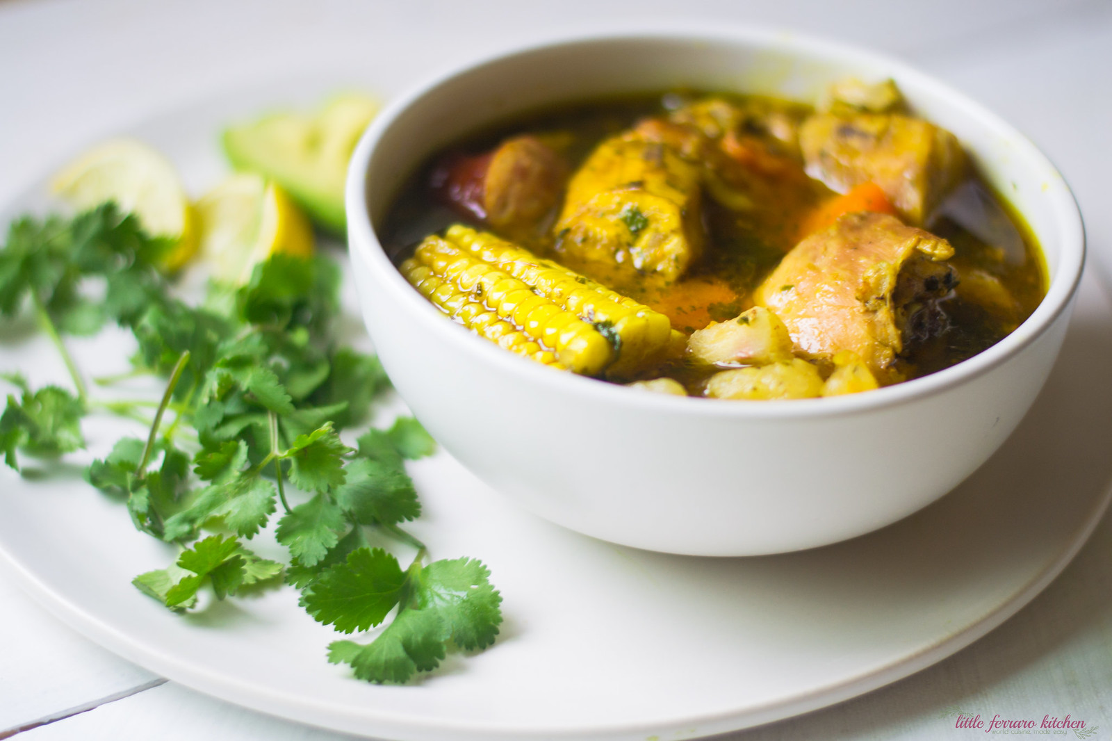 Serve sancocho recipe with lime and sliced avocado.