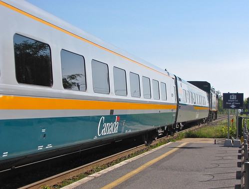 A bright and clean looking VIA Rail train pulls away from a station platform on a sunny day