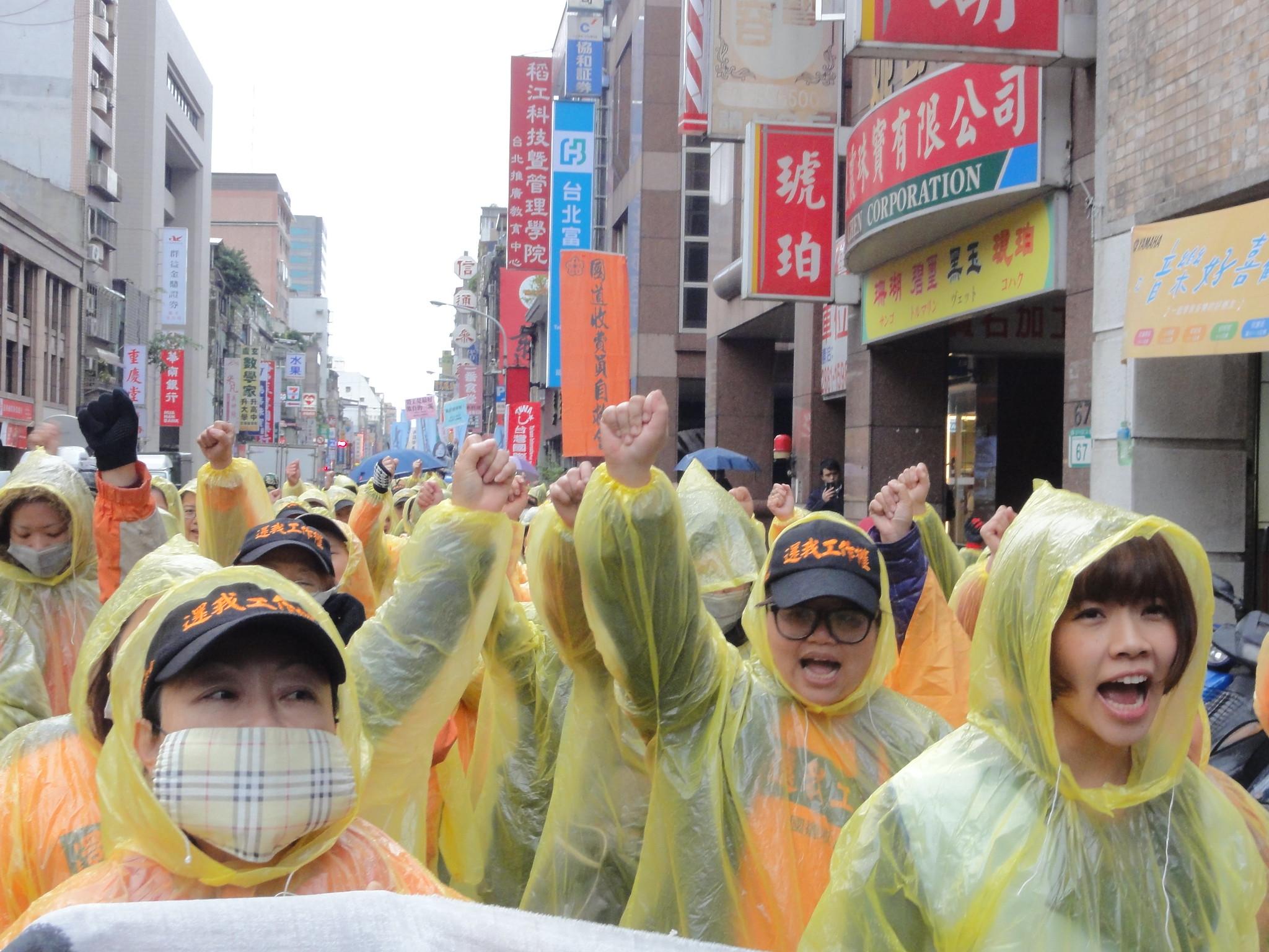 雨中遊行的勞工們。(攝影:張智琦)