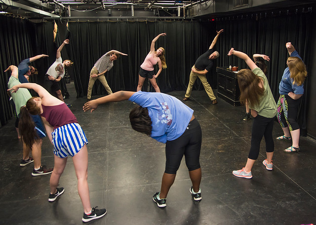 A group of theatre students and their professor stand in a circle as they stretch by leaning to the left.