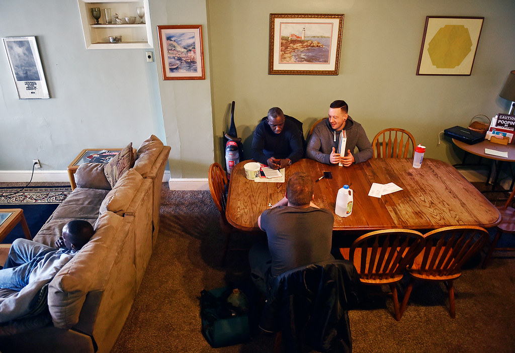 © 2016 by The York Daily Record/Sunday News. Anthony McClair, 50, originally of Bronx, N.Y., and Nathan Embry, 27, of Lancaster, review McClair's federal taxes while Will Howard, 54, of Philadelphia, far left, watches TV and Jake Miller, 32, of West York, waits for the weekly house meeting to begin at the Linden Avenue recovery house operated by Sees-the-Day, on Sunday, Feb. 28, 2016.