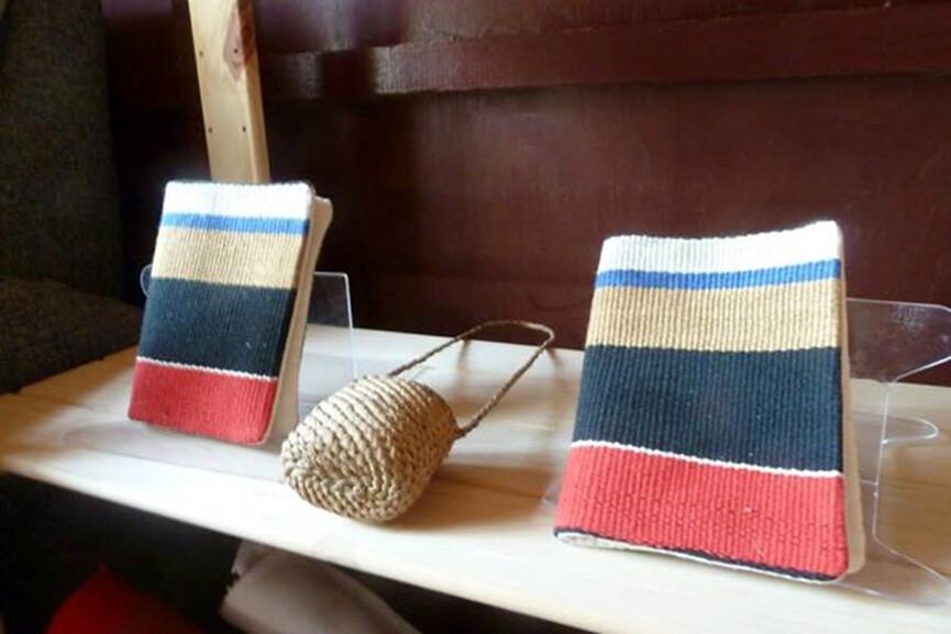 Ina編織的書套及小提袋,放在工作室外頭的展示架上,讓路過此地的觀光客愛不釋手。攝影:劉欣宜。