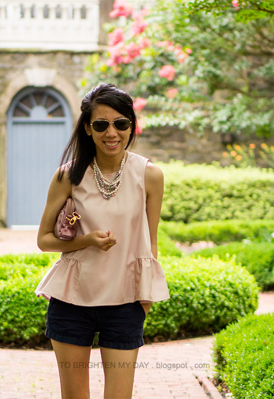 pearl and mixed metal necklace, pink peplum top, navy shorts, rose pink clutch