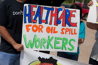 'Healthcare for Oil Spill Workers' sign among many at the 3-State Press Rally for Fisherfolk in Biloxi, MIssissippi - TEDx Oil Spill Expedition | by Kris Krug