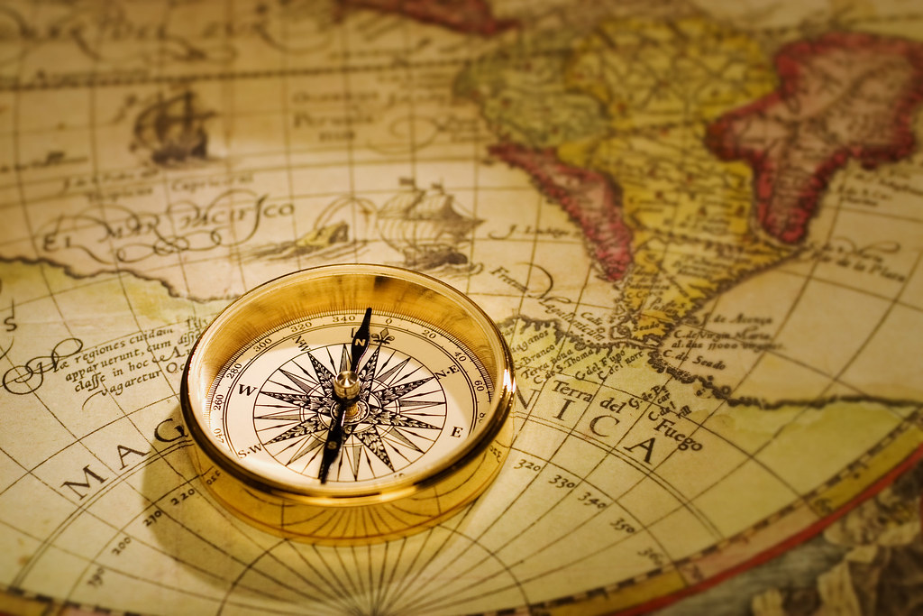 Compass and Antique Map   An antique gold compass set upon ...
