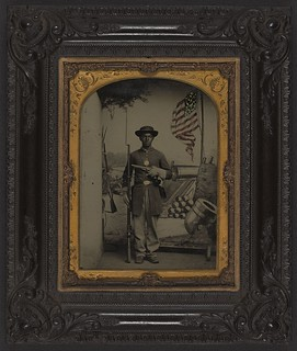 [Unidentified African American Union soldier with a rifle and revolver in front of painted backdrop showing weapons and American flag at Benton Barracks, Saint Louis, Missouri] (LOC) | by The Library of Congress