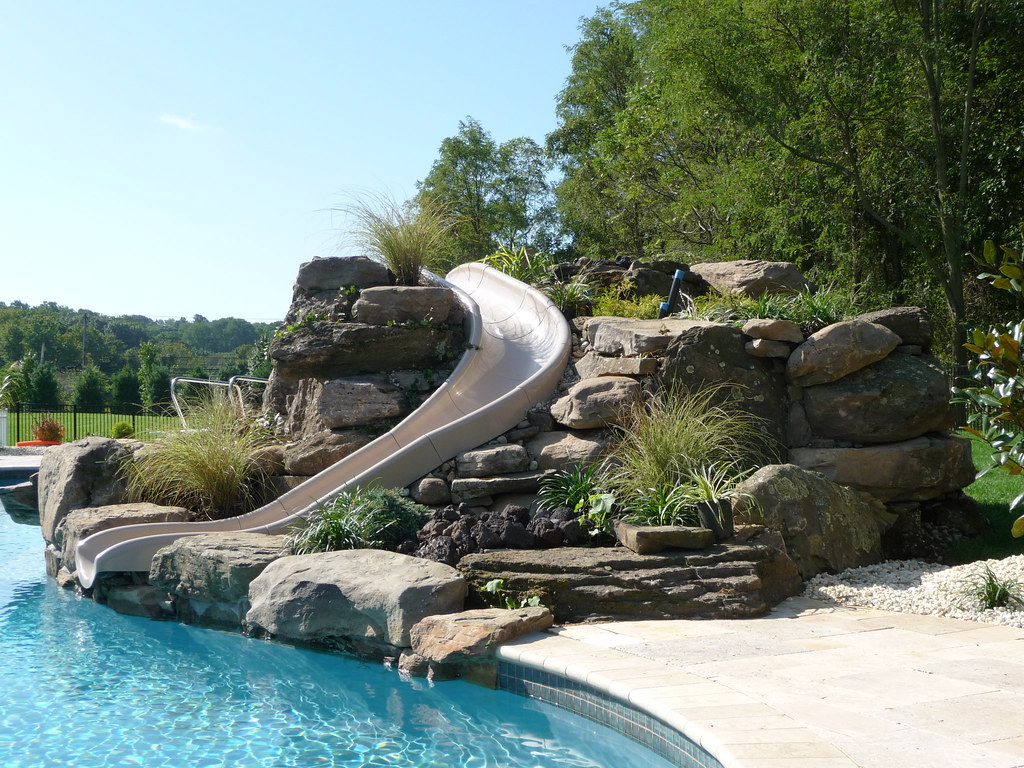 Photo custom natural stone waterfall pool slide and pave for Natural rock swimming pools