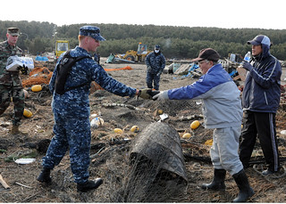 Sailor returns netting to Japanese man during cleanup at Misawa, Japan following earthquake. | by Official U.S. Navy Imagery