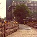 Restoration and expansion of the Bowling Green in Lower Manhattan. Two workers have a chat while a red 1970s pickup truck navigates the narrow streets. Trees from Battery Park in the distance. New York. June 1974