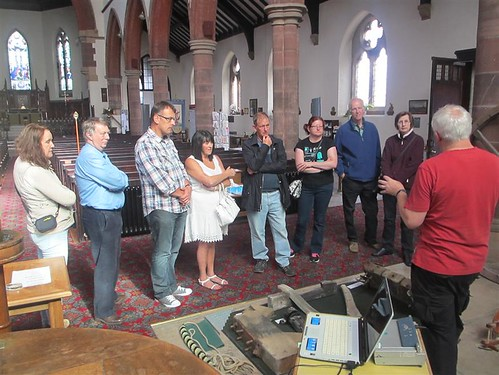 Group of visitors on tower tour listen to Andy giving talk and using old bell parts to explain