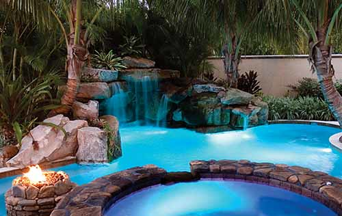 Swimming pool with natural stone grotto waterfall by lucas for Stone swimming pool
