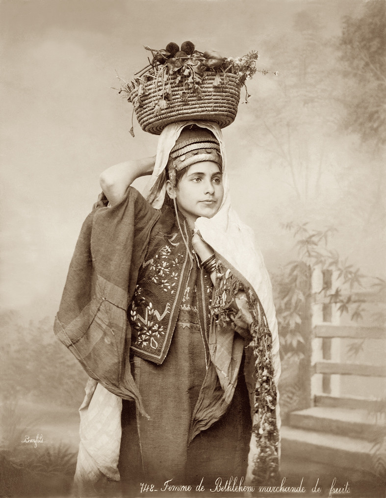 a woman with a basket of fruit on her head